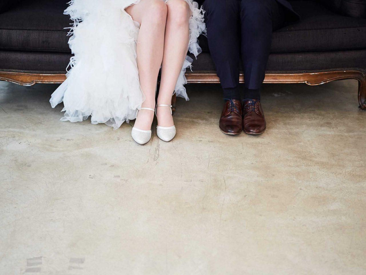 Hochzeitspaar auf Couch mit Tanzschuhen