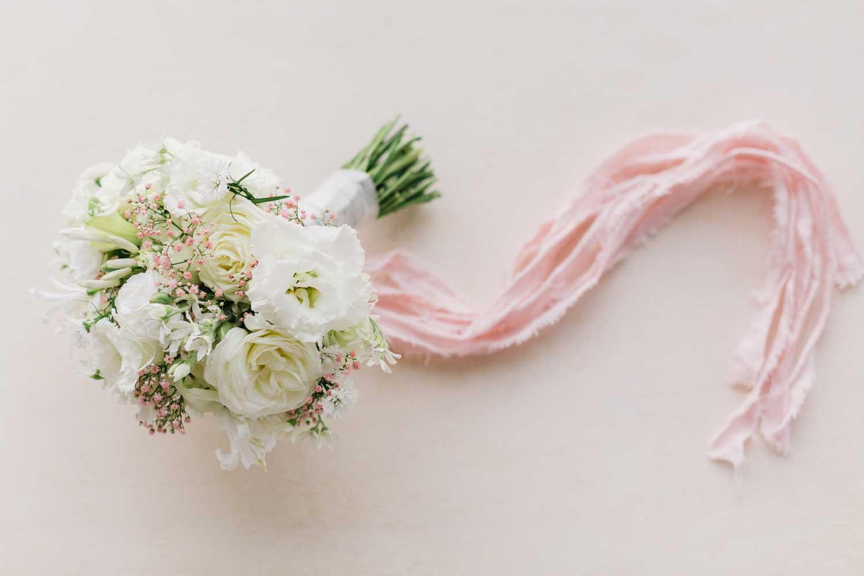 Brautstrauß in Weiß mit rosa Bändchen