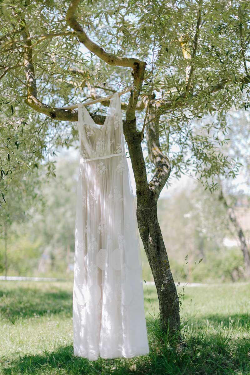 Brautkleid hängt an Kleiderbügel im Baum.