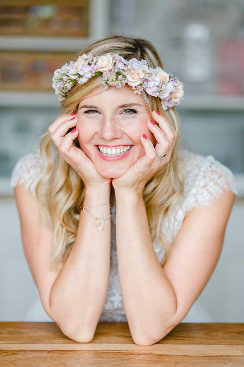 Lachende Braut stütz sich auf Tischplatte ab mit Blumjenband im Haar.