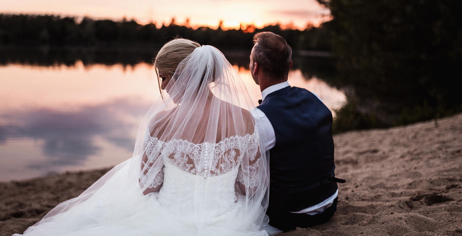 Hochzeitspaar blickt auf Sonnenuntergang